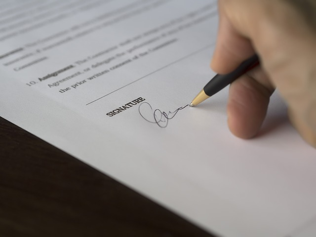 Person signing a document in a benefit fraud